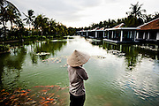A vietnamese woman stands in front of a pond at the Nam Hai resort, Hoi An, Vietnam, Southeast Asia