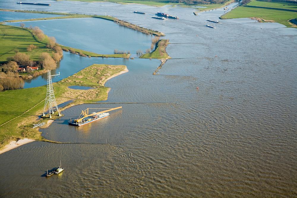 Nederland, Gelderland, Bommelerwaard, 11-02-2008; hoogspanningsmast vlakbij het plaatsje Heesselt aan de oever van de rivier de Waal (tegenover Hurwenen); in december 2007 is hier een Apache-gevechtshelikopter tegen de hoogsapnningskabel gevlogen, de mast is drie maanden later slechts gedeeltelijk hersteld. Continuon, de netbeheerder van elektriciteitsbedrijf NUON, heeft een schadeclaim bij het ministerie van defensie ingediend; scheepvaartverkeer op de rivier, binnenvaart, Tielerwaard, energie, elektriciteit, electriciteit, hoogspanning, koppelnet, hoogspanningsmast, hoogspanningsdraden, stroom,  energievoorziening; ongeluk, ongeval, helicopter, apache..luchtfoto (toeslag); aerial photo (additional fee required); .foto Siebe Swart / photo Siebe Swart