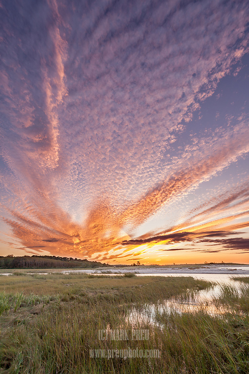 A fiery sunset illuminates the sky over Paine's Creek in Brewster.