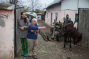 Mother Gabriela Costache (37,2nd left), her 17 years old daughter in law Maria Bondaret and Mr. Costache with horse Corina at the entrance to their property.