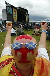 Fan at the main stage with his hair dyed with a 'T', at T in the Park, July 10, 2004..©Michael Schofield.