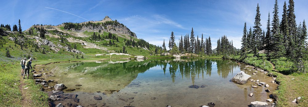 Hikers admire Naches Peak reflected in a pond along the Pacific Crest Trail in Mount Rainier National Park, Washington, USA. The Naches Peak Loop Trail is a 5 mile loop starting near Chinook Pass on Highway 410 between Enumclaw and Yakima. This panorama was stitched from 9 overlapping photos.