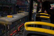 London buses and yellow seating handles from the top deck of a double-decker.