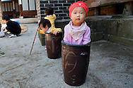 "Jung Ha-yoon, 2, appears to be stuck inside a ceramic container traditionally used to ferment Kimchi, while playing with other children at the traditional sports square during the ""Taste Korea! Korean Royal Cuisine Festival"" held at Unhyeon Palace, also known as Unhyeongung Royal Residence, in Seoul, South Korea, on Tuesday, Oct. 1 2013. (AP Photo/Jacquelyn Martin)"