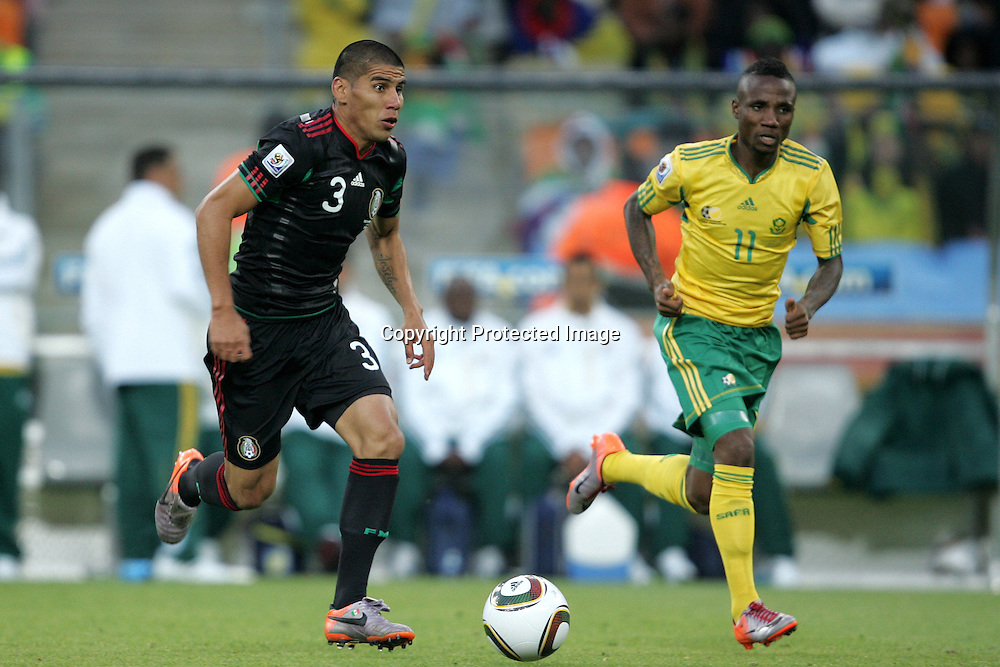 Carlos SALCIDO attacks as Teko MODISE gives chase during the opening match ( match 1) of the FFA World Cup 2010 South Africa held at Soccer City in SOWETO, Johannesburg, South Africa on the 11th June 2010<br /> <br /> Photo by Ron Gaunt/SPORTZPICS