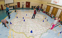 Brayden in Alaska, Sarah in Greenland, Cayden in California and Olivia in Florida measure the distances with Dalton naming North Dakota as the middle point with Phys Ed Teacher Mrs. Nims and Principal Sheila Arnold as the Belmont Elementary 2nd graders work with the interactive North American Map on Thursday afternoon.  (Karen Bobotas/for the Laconia Daily Sun)