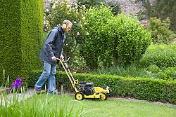 Gardener using lawn edging machine at Sissinghurst Castle Garden