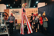 Kelsey Petron, 20, from right, Brittany Friedrich, 19, Gretchen Lueck, 18, and Kalee Petron, 19, all members of the Minnesota College of Republicans at St Mary's University of Minnesota, get ready to pose in a photo booth with stilt walkers in the HUB during day two of the Conservative Political Action Conference (CPAC) at the Gaylord National Resort & Convention Center in National Harbor, Md.