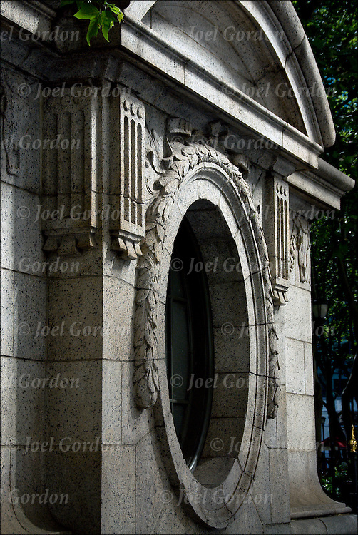 Architecture detail of exterior building oval window with garland and round cornice by Carrire and Hastings, nineteen century architects of the New York Public Library