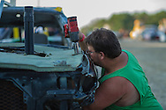 A competitor in the demolition derby tighten up the hood on his car at Summitt County Fairgrounds, Thursday, July 26, 2016 in Tallmadge, Ohio. All cars participating had previously been used in at least one demoltion derby.