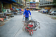 "11 DECEMBER 2012 - BANGKOK, THAILAND: A worker pushes a cart of cables used in demolition through the empty buildings at ""Washington Square"" a notorious entertainment district off Sukhumvit Soi 22 in Bangkok. Demolition workers on many projects in Thailand live on their job site tearing down the building and recycling what can recycled as they do so until the site is no longer inhabitable. They sleep on the floors in the buildings or sometimes in tents, cooking on gas or charcoal stoves working from morning till dark. Sometimes families live and work together, other times just men. Washington Square was one of Bangkok's oldest red light districts. It was closed early 2012 and is being torn down to make way for redevelopment.    PHOTO BY JACK KURTZ"