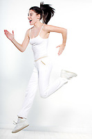 one beautiful young caucasian woman runner running jumping happy on studio isolated white background