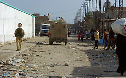 .British soldiers from the Duke of Wellington's Regiment wearing desert camouflage, and body armor, carrying SA80 assault rifles which are fitted with SUSAT sights,on a foot patrol through the streets of a viliage near Shia Flats gathering low level intelligence through speaking with locals, during Op-Telic in March 2005.