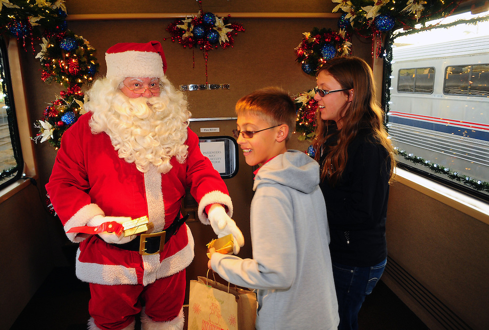 "Santa presents gifts to 12-year-old Andrew Wormley, and his 14 year-old sister Alex, while on board the BNSF Railway ""Holiday Express"" on Tuesday  December 4, 2012. The railway company offered 300 military families a 90-minute ride on the the specially decorated train.   (Adolphe Pierre-Louis/Journal)"