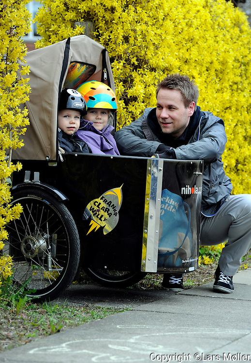 DK:<br /> 20100428, K&oslash;benhavn, Danmark.<br /> Mark B&ouml;rresen med sine b&oslash;rn Clara og William k&oslash;rer i cykelvogn<br /> Foto: Lars M&oslash;ller<br /> UK: <br /> 20100428, Copenhagen, Danmark.<br /> Biking: Mark B&ouml;rresen (riding the bike) and his kids William and Clara in the box looking at a women showing tricks with her dog<br /> Photo: Lars Moeller