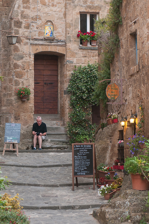 A tourist relax on some stairs of the village of Civita di Bagnoregio.<br /> Civita di Bagnoregio is a town in the Province of Viterbo in central Italy, a suburb of the comune of Bagnoregio, 1 kilometre (0.6 mi) east from it. It is about 120 kilometres (75 mi) north of Rome. Civita was founded by Etruscans more than 2,500 years ago. Bagnoregio continues as a small but prosperous town, while Civita became known in Italian as La citt&agrave; che muore (&quot;The Dying Town&quot;). Civita has only recently been experiencing a tourist revival. The population today varies from about 7 people in winter to more than 100 in summer.The town was placed on the World Monuments Fund's 2006 Watch List of the 100 Most Endangered Sites, because of threats it faces from erosion and unregulated tourism.
