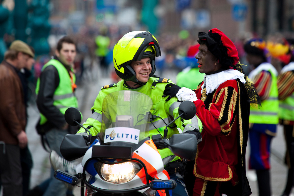 Black Pete with motorcycle policeman at Sinterklaas parade, Dam Square, Amsterdam, 14th November 2010