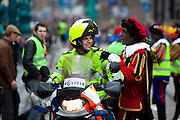 Black Pete with motorcycle policeman at Sinterklaas parade, Dam Square, Amsterdam, 14th November 2010