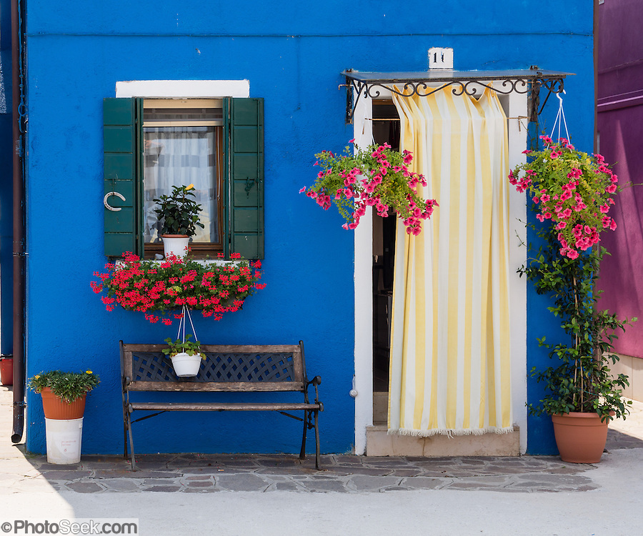 "Blue house with striped yellow curtain. Burano, known for knitted lacework, fishing, and colorfully painted houses, is a small archipelago of four islands linked by bridges in the Venetian Lagoon, in the Veneto region of Italy, Europe. Burano's traditional house colors are strictly regulated by government. The Romans may have been first to settle Burano. Romantic Venice (Venezia), ""City of Canals,"" stretches across 100+ small islands in the marshy Venetian Lagoon along the Adriatic Sea in northeast Italy, between the mouths of the Po and Piave Rivers. Venice and the Venetian Lagoon are honored on UNESCO's World Heritage List."