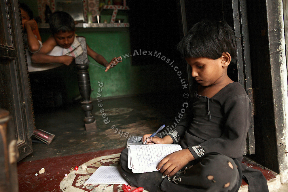 Nusarat, (right) 7-year-old girl from the village of Barnawa, pop.6000, Baghpat District, Uttar Pradesh, India, located along the banks of the severely polluted Hindon river, is completing her homework while her brother, Sahanawaj, 9, is playing on a bed inside their house, on Thursday, Apr. 17, 2008. Both children cannot either speak or hear, while their younger brother, Sarik, 4, was born with a neurological disorder that have left him unable to walk and with minor cognitive skills. The family laments the water delivered from their hand-pump to be yellow at times and of a particular, different odour and taste.