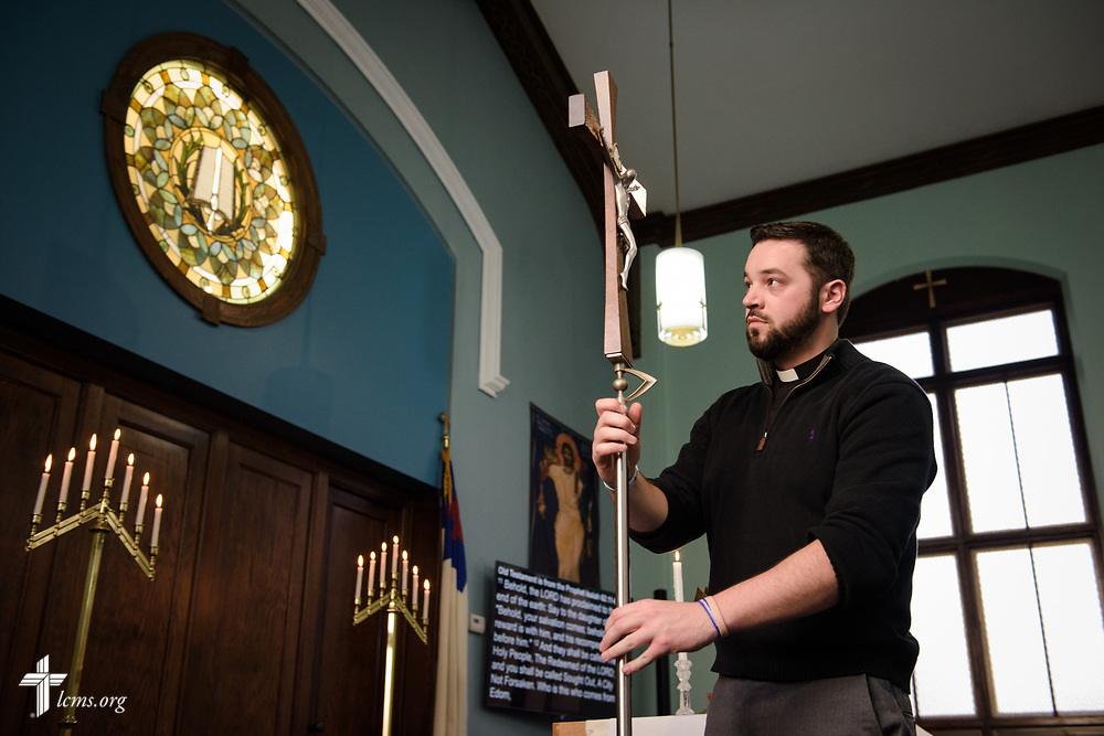 SMP Vicar Tyler Cronkright places the processional cross next to the altar during the chancel dedication service at Family of God on Wednesday, March 28, 2018, in Detroit. LCMS Communications/Erik M. Lunsford