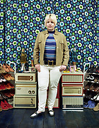 Young woman standing in front of vintage floral patterned wallpaper and vintage amps.