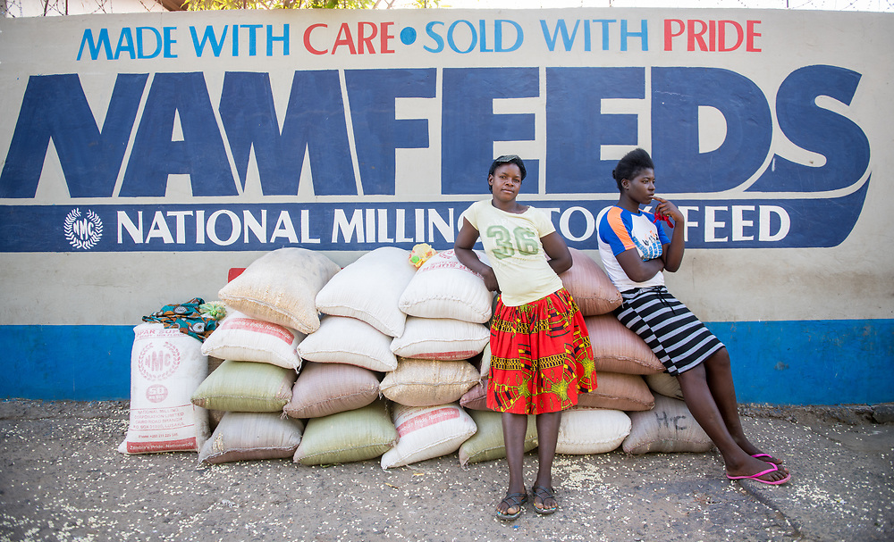 Mother'sTwo young Zambian women stand in front of bags of National Milling Corporation Limited grain. Livingstone, Zambia