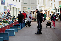 02 April 2020. Hesdin, Pas de Calais, France. <br /> Coronavirus - COVID-19 in Northern France.<br /> <br /> Easing restrictions on local markets. For the first time since government restrictions came into force, the main market in Hesdin has been permitted to re-open. Blue produce crates mark the distance people must maintain to keep to 'social distancing' guidelines.<br /> The historical town has hosted a usually vibrant and bustling market since the middle ages. With stall holders limited and many suffering huge financial losses, those selling food today were happy to be back to work despite the ongoing risks posed by coronavirus.<br /> <br /> Shoppers, many wearing masks were mostly maintaining their social distancing with people happy to be out and able to meet and talk with other people. A lot of shoppers were elderly people who have been trapped in their homes for weeks. One shopper complained of 'la misère,' - the misery of this virus and being stuck in her home. <br /> <br /> Anyone leaving their home must carry with them an 'attestation,' in a effect a self administered permit to allow them out of the house. If stopped by the police, one must produce a valid permit along with identification papers. Failure to do so is punishable with heavy fines. Movement in France has been heavily restricted by the government and today's market re-opening was a brief return to normalcy for many able to escape the confines of their homes.<br /> <br /> Photo©; Charlie Varley/varleypix.com