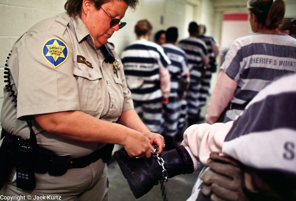"01 NOVEMBER 1999  - PHOENIX, ARIZONA, USA: A detention officer in the Maricopa Country Jail in Phoenix, AZ, inspects women prisoners who are on the county's chain gang before taking them out on the streets to perform public service clean up. Maricopa county sheriff Joe Arpaio claims to have the only women's chain gang in the United States. He has been criticized for the chain gang but claims to be an ""equal opportunity incarcerator."" He has said that if puts men on a chain gang he will also put women on a chain gang. © Jack Kurtz  WOMEN   PRISON   CIVIL RIGHTS  SOCIAL ISSUE"