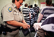 """01 NOVEMBER 1999  - PHOENIX, ARIZONA, USA: A detention officer in the Maricopa Country Jail in Phoenix, AZ, inspects women prisoners who are on the county's chain gang before taking them out on the streets to perform public service clean up. Maricopa county sheriff Joe Arpaio claims to have the only women's chain gang in the United States. He has been criticized for the chain gang but claims to be an """"equal opportunity incarcerator."""" He has said that if puts men on a chain gang he will also put women on a chain gang. © Jack Kurtz  WOMEN   PRISON   CIVIL RIGHTS  SOCIAL ISSUE"""