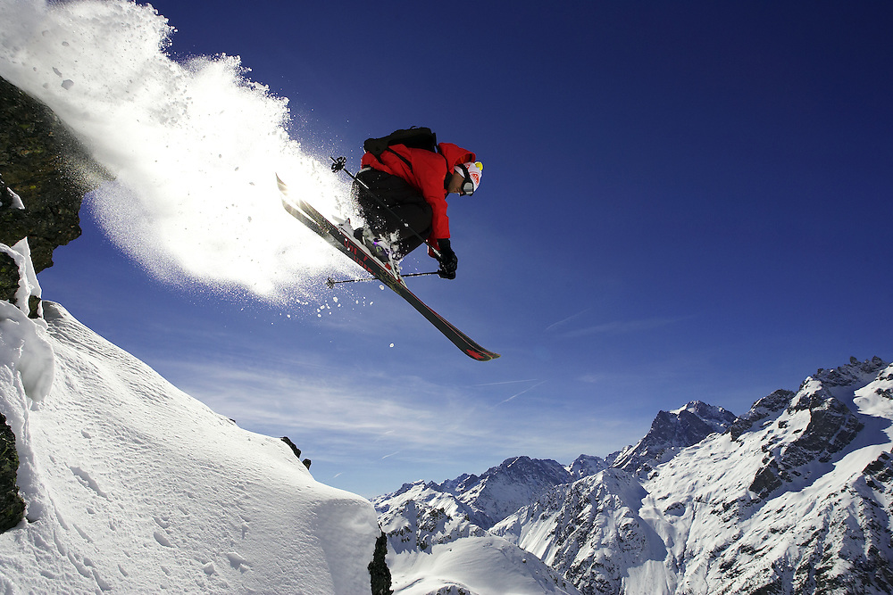 Male skier jumps from rock on mountainside, Serre Chevalier, France