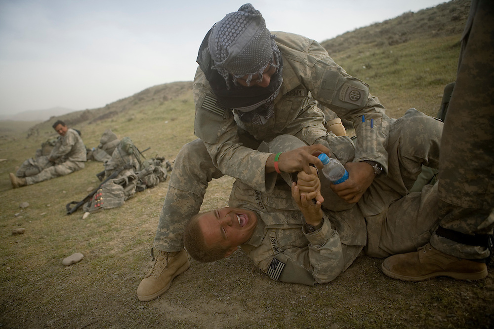 Private Luis Moreira, top, and Sargeant Wesley Rinehart of the 82nd Airborne, 1/508 Parachute Infantry Regiment, Alpha Company, Third Platoon wrestle at Forward Operations Base Diablo in Kandahar province on Friday, March 30, 2007.
