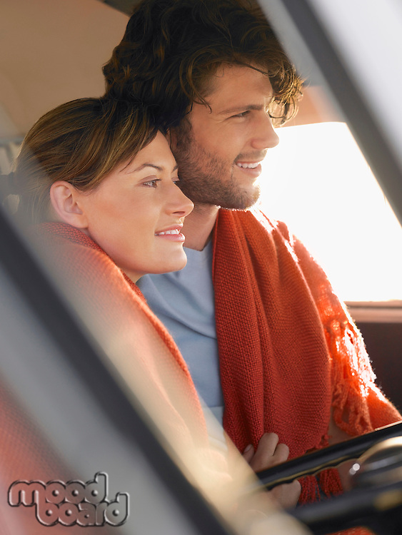 Couple wrapped in blanket in front seat of van profile