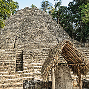 Steps of La Iglesia in the background. The small structure with the thatched roof in the foreground has been designated as Stela 11 at Coba, an expansive Mayan site on Mexico's Yucatan Peninsula not far from the more famous Tulum ruins. Nestled between two lakes, Coba is estimated to have been home to at least 50,000 residents at its pre-Colombian peak.