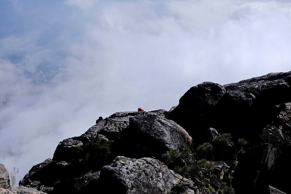 Table Mountain,Cape Town, South Africa. Climbers appear over the edge of the rock face as they approach the top of table mountain.