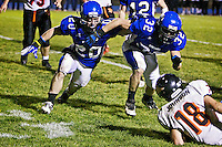 Coeur d'Alene High's Jake Cheesman, left, and J.J. Johnson race in to down a Post Falls player during their game Oct. 21.