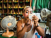 "30 JANUARY 2016 - NONTHABURI, NONTHABURI, THAILAND:  A performer puts on his makeup before a ""likay"" show at Wat Bua Khwan in Nonthaburi, north of Bangkok. Likay is a form of popular folk theatre that includes exposition, singing and dancing in Thailand. It uses a combination of extravagant costumes and minimally equipped stages. Intentionally vague storylines means performances rely on actors' skills of improvisation. Like better the known Chinese Opera, which it resembles, Likay is performed mostly at temple fairs and privately sponsored events, especially in rural areas. Likay operas are televised and there is a market for bootleg likay videos and live performance of likay is becoming more rare.    PHOTO BY JACK KURTZ"