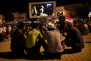 Kashgar: Uighur men and families gather on Id Khar Mosque square nightly to watch Uighur TV broadcast TV shows and films on giant screen in the square...Despite the migration of millions of Han Chinese to the western part of the Xinjiang Uighur Autonomous Region, the Uighur community continue to practice their muslim culture and resist the suppression of their cultural and religious traditions by the Chinese government....The chinese government has been criticised for the redevelopment of the old city, which has involved the destruction of many of the old houses in the town that were built without regulation, officials claiming them to be overcrowded and uncompliant with earthquake codes...Many in the chinese government believe Kashgar to a breeding ground for Uighur separatists, who Beijing claim to have links to terrorism...The european parliament has called for a halt to the cultural destruction of Kashgar, suggesting that Kashgar be added tot he UNESCO World heritage 'Silk Road' project, and calling on the chinese government to develop a genuine Han-Uighur dialogue to adopt more inclusive and comprehensive economic policies in Xinjiang in order to protect the cultural identity of the Uighur population..©JTanner/July 2011