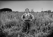 Mitsuo Takeno stands in his fallow field of weeds where rice used to grow right on the nuclear no-entry zone line 12 km. (9.3 miles) from the crippled Fuksushima Daiichi nuclear power plant.  Since April, the no-entry was pushed back to the Minami-Soma - Namie-machi line and he can return to clean his house but cannot yet live there or farm.  His house lacks running water and with radiation contaminated fields, he cannot farm.  Mr. Takeno lives in an evacuation center in the northern part of Minami-Soma.  Odaka Village, Minami-Soma City, Fukushima Prefecture, Japan.