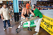 July 13, 2008 -- PHOENIX, AZ: Luchadors (wrestlers) Dr. Parker beats up Fly Boy with a folding chair from the audience during a Lucha Libre show at El Gran Mercado in Phoenix. Parker was the rudo (villian) in the bout, Fly Boy the tecnico (good guy). The man on the left is a spotter who makes sure the Luchadors don't hurt anyone when they fly out of the ring. Lucha Libre is Mexican style wrestling. There are heros (Tecnicos) and villians (Rudos). The masks are popular as children's gifts and tourist mementos. As the size of the Mexican community in the Phoenix area has grown, attendance at the Lucha Libre shows has increased. Lucha Libre differs from American style entertainment wrestling in several ways, but principally the wrestlers are more acrobatic and rely less on body slams than American wrestling. The shows, which used to be held only periodically, are now held every week at El Gran Mercado, a flea market and swap meet that caters mostly to the Mexican community in Phoenix.   Photo by Jack Kurtz / ZUMA Press