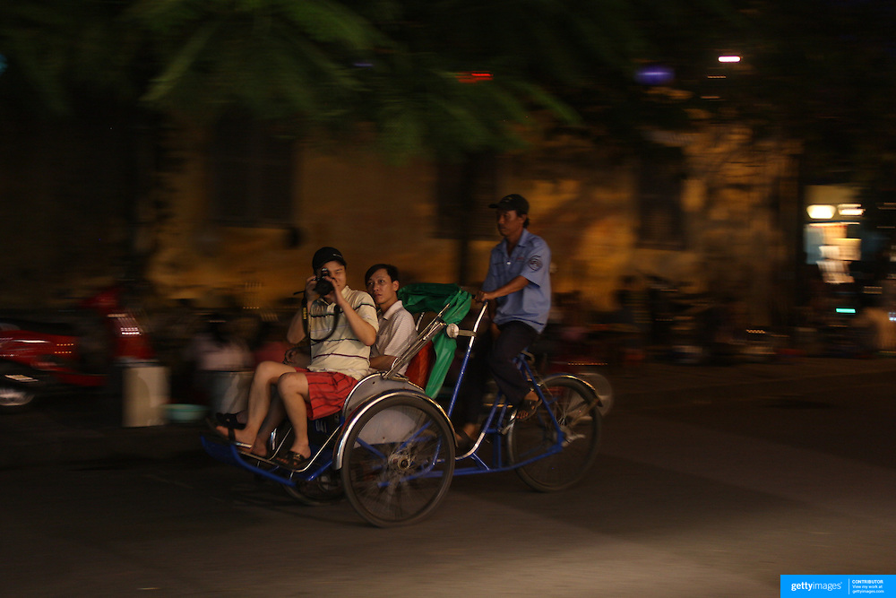 A street scene in Hoi An, Vietnam showing tourists riding a cycle in the early evening. Hoi An is an ancient town and an exceptionally well-preserved example of a South-East Asian trading port dating from the 15th century. Hoi An is now a major tourist attraction because of its history. Hoi An, Vietnam. 5th March 2012. Photo Tim Clayton