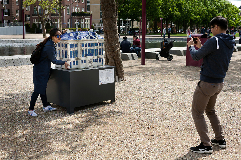 Asian tourists in amsterdam photographing with house object