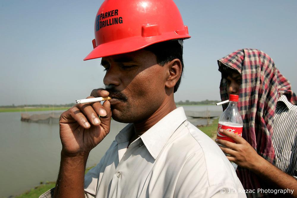 BANGLADESH HABIGANJ BIBIYANI 23FEB05 - Crane driver Youssef and assistant Rumi (L-R) enjoy a cigarette break near Bibiyana Gas Field, owned by Unocal, in northern Bangladesh..jre/Photo by Jiri Rezac ..© Jiri Rezac 2005..Contact: +44 (0) 7050 110 417.Mobile:  +44 (0) 7801 337 683.Office:  +44 (0) 20 8968 9635..Email:   jiri@jirirezac.com.Web:    www.jirirezac.com..© All images Jiri Rezac 2005- All rights reserved.