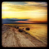 Hampton Bays, NY: July 26, 2014--- As the sun sinks in the west this Hampton Bays beach takes on golden tones during a spectacular Long Island sunset on the Peconic River. © Audrey C. Tiernan