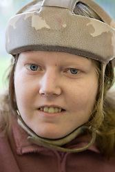 Portrait of a young woman with learning disability wearing a helmet to protect her head,