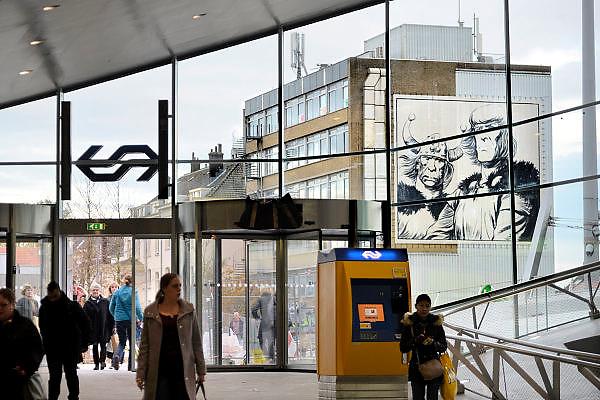 Nederland, the Netherlands, Arnhem, 1-9-2015Het nieuwe station van de gelderse hoofdstad wordt binnenkort officieel geopend. De ov terminal met parkeergarage en fietsenstalling is klaar. De ingewikkelde architectuur heeft het bouwproject veel problemen en vertraging opgeleverd. Het is dan ook een architectonisch en bouwkundig hoogstandje. Het ontwerp voor het station is gedaan door architectenbureau UNStudio, Ben van Berkel.  Uiteindelijk heeft de bouw 18 jaar en 90 miljoen euro, veel meer als aanvankelijk begroot, gekost. Meteen deden zich al enkele valpartijen voor op een van de onregelmatige trappen, zodat een opgang tijdelijk afgesloten werd totdat er duidelijke trapmarkering is aangebracht...Vanuit de hal is op een gevel buiten een striptekening van Eric de Noorman te zien. Hans Kresse.FOTO: FLIP FRANSSEN/ HH