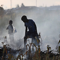 050709_Lusaka, Zambia Melanie Maxwell <br /> Two young boys pick through a smoldering pile of garbage in a compound in Lusaka, Zambia on Thursday, May, 7 2009.