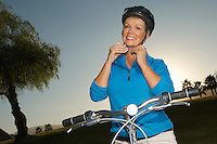 Senior woman adjusting cycling helmet at dusk, portrait