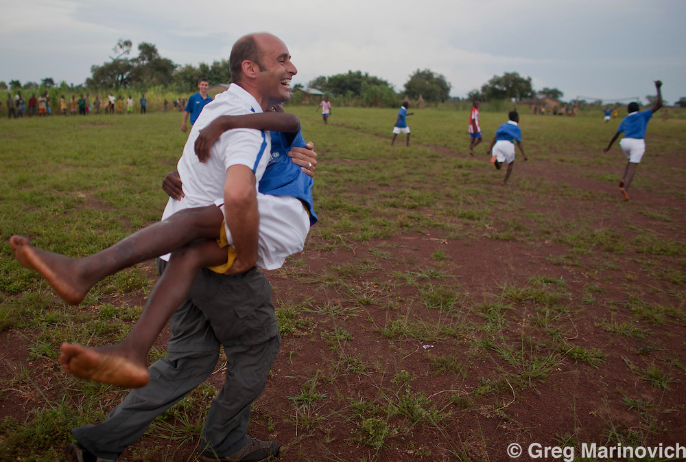 Glasgow Rangers CEO Martin Bain  celebrates a goal with children who have been given Glasgow Rangers football kit on a  trip to Togo with UNICEF to see where the Rangers charity foundation will assist with building and funding clinics in remote areas. Jack Bain, Martin's son is at rear left partially obscured. Photo: Greg Marinovich / StoryTaxi / UNICEF