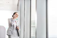 Smiling young businesswoman talking on cell phone near office window